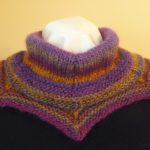 A snug cowl that fans out over the shoulder, coming to six points at the lower edge. The yarn naturally forms rings of gold, purple, lavender and olive green.