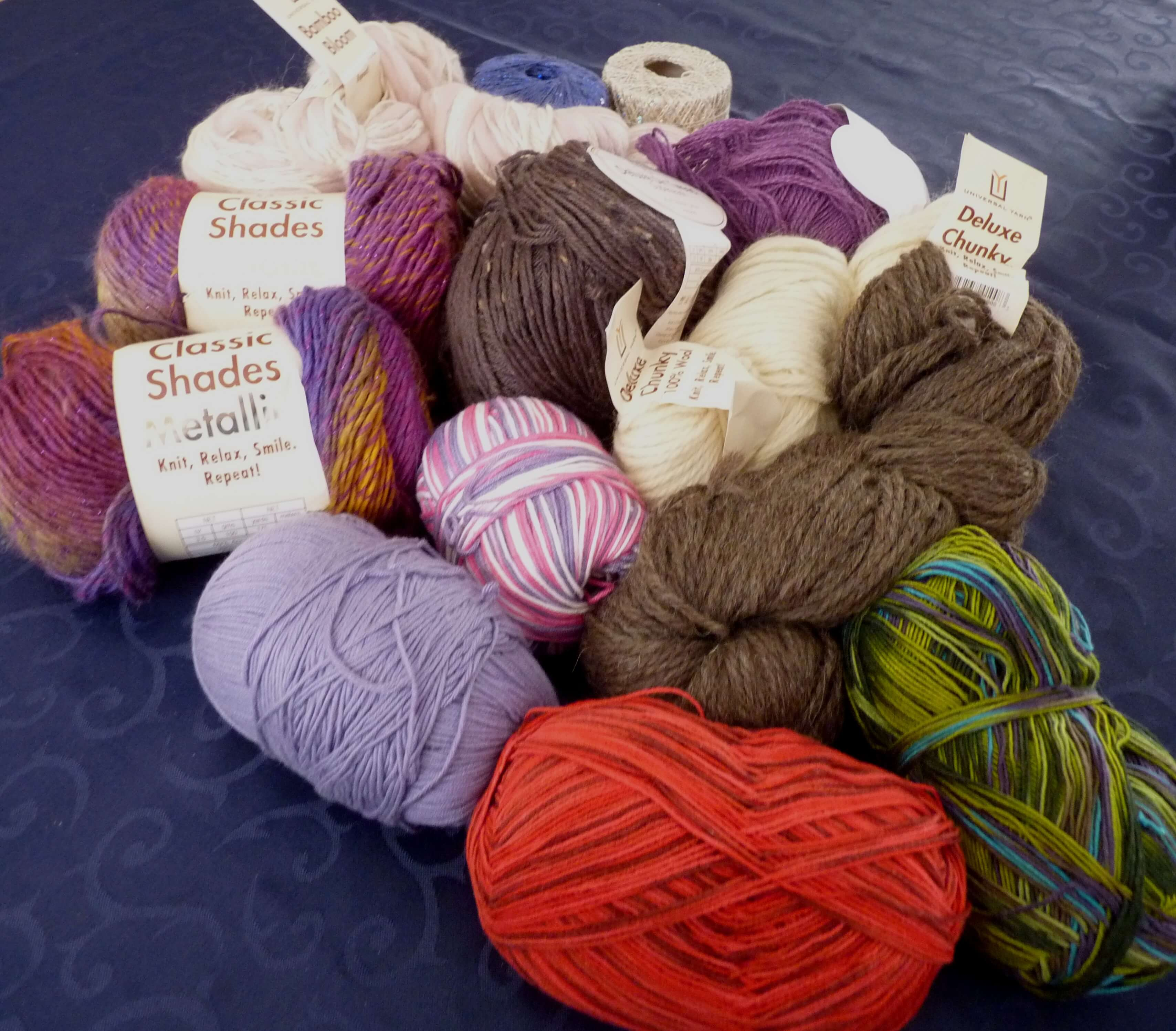 A jumble of yarns of various colours, some in balls (sock yarn, worsted weight in a purple variegated yarn) and skeins (Bamboo bloom and natural chunky in natural white and brown.