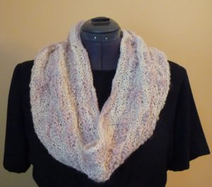 A pink and white cowl on a dress form.