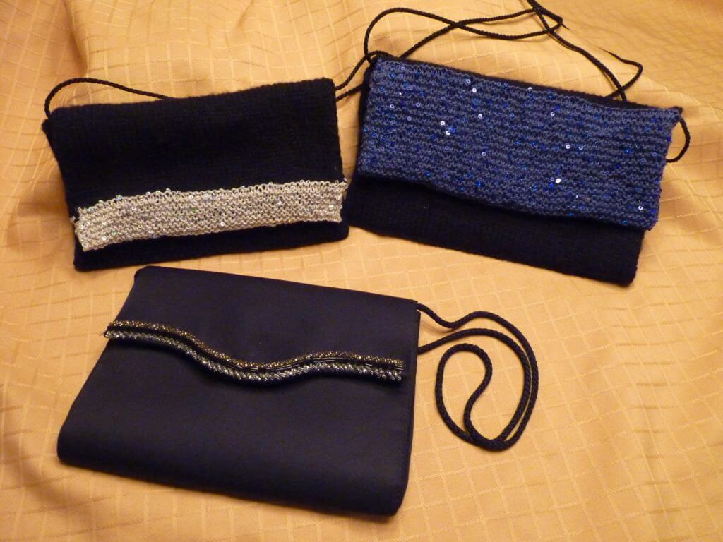 Three evening bags. In the foreground is a black one that inspired the two knitted ones, both black with sequinned trim, one with a narrow band of silver and the other a wide band of blue.