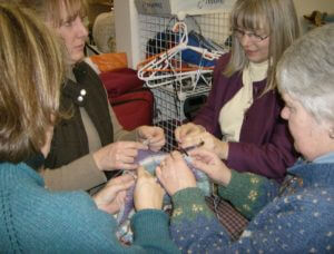 Four knitters working on one piece of knitting, which is growing from the centre out.