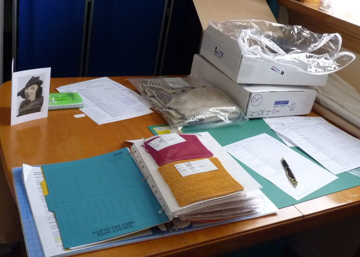 A table covered with materials - a binder with samples, pages of evaluation forms, and packaging material