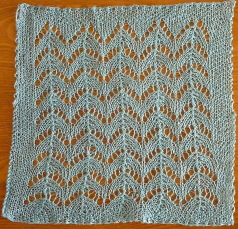 a soft, blue-green coloured tension swatch in a lace pattern that has columns of double decreases and graceful arcs of eyelets, with a seed stitch border