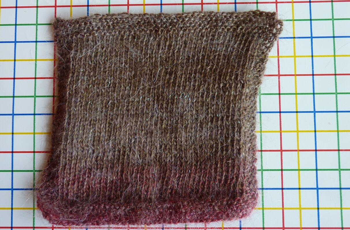 A swatch of stocking stitch fabric on a checked background.. The lines on the background show just how off-square the stocking stitch knitting is. It leans to the right like a parallelogram!