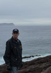 A man standing on a rocky shore with small waves splashing white on the rocks. In the distance there is a misty piece of land's end and clouds and mist over the Atlantic Ocean.