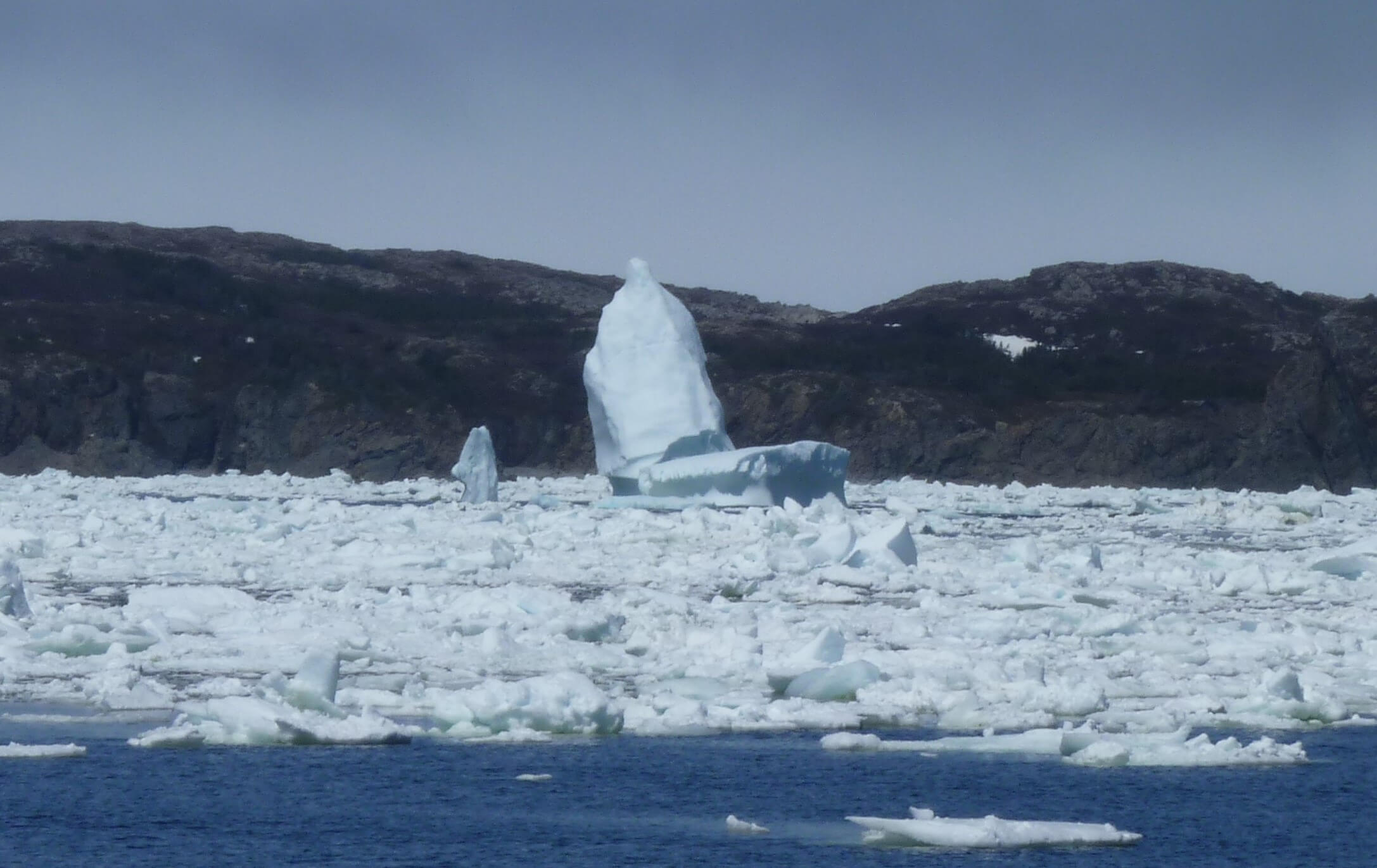 An iceberg in a bay that reaches higher than the hills on the opposite side of the bay.