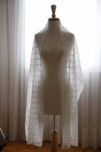 A lacy linen stole draped over a dress form, lit from a window covered in sheer curtains behind it.