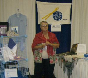 Bonnie wearing a red mohair shawl, standing in a booth with CGK's original knitted sign.