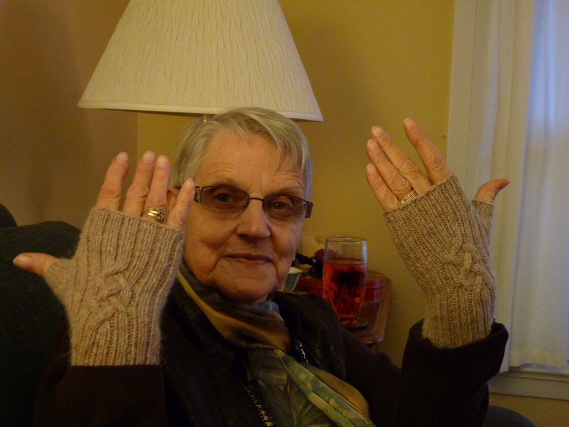 Bonnie, holding up her hands to show a pair of hand knit fingerless mitts in beige yarn