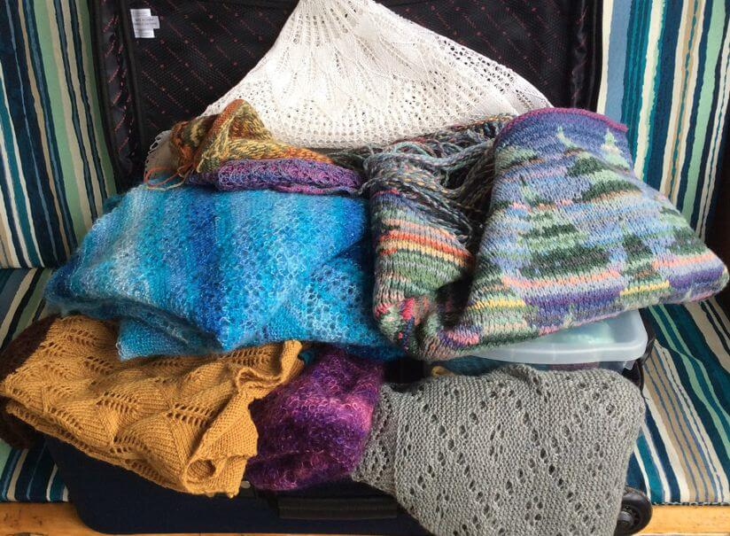 An open suitcase overflowing with shawls in all shapes, sizes, and colours, with a clear plastic box of sample shawls peeking out between the layers of shawls
