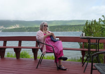 Cynthia in a pink sun dress, knitting on a deep red stained deck, with Lake Bras d'Or in the background.