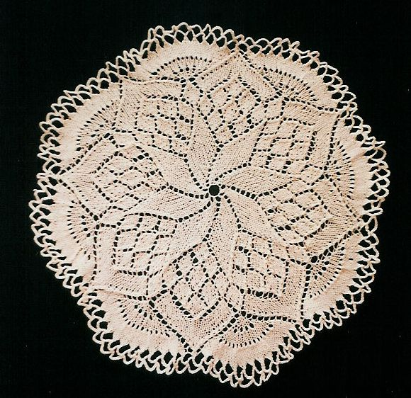 A white doily with a crochet loop edging on a black background. The doily starts with a swirl in the centre, and ends up as an 8-pointed flower with scallops between the petal tips.