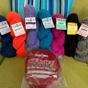 """skeins of yarn lined up on an olive green chair with a red """"cake"""" of B&L's Country Roving in the foreground. The skeins are Durasport (in navy), Sport (in hunter's orange), Regal in Fundy Fog, Heritage in Quoddy Blue, Tuffy in magenta, Atlantic (black) and Super (grey heather)"""