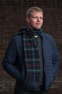 A model wearing a navy quilted jacket and a McKenzie tartan scarf which features red and white lines intersection on a ground of green, navy and black.