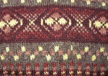 """a traditional Fair Isle knitting design in the X & O pattern, with a chequerboard """"peerie"""" pattern below and a corrugated ribbing at the bottom of the photo. The yarns are in shades of brown and rust, with a pale, buttery yellow highlighting the patterns."""