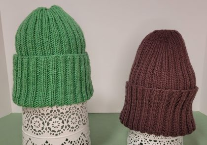 two hats are placed over lacy forms sitting on a green tablecloth. The hat on the left is green, and the one on the right a chocolate brown.